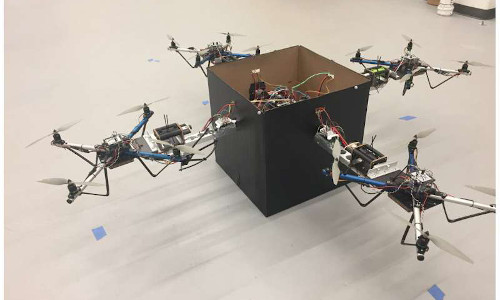 Multiple drones team up to lift a box.
